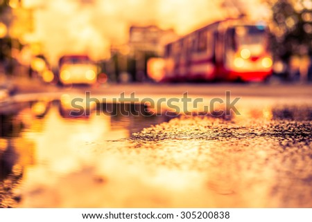 Sun after the rain in the city, view of the approaching tram with a level of puddles on the pavement. Image in the yellow-purple toning - stock photo