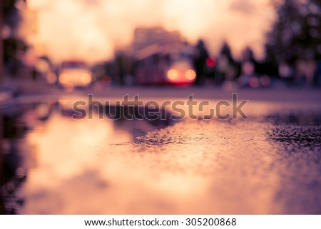 Sun after the rain in the city, view of the approaching tram with a level of puddles on the pavement. Image in the soft orange-purple toning - stock photo