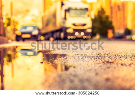 Sun after the rain in the city, view of the approaching truck with a level of puddles on the pavement. Image in the yellow-purple toning - stock photo
