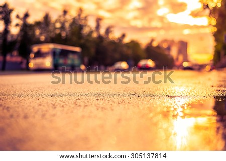 Sun after the rain in the city, view of the bus with a level of puddles on the pavement. Image in the orange-purple toning - stock photo