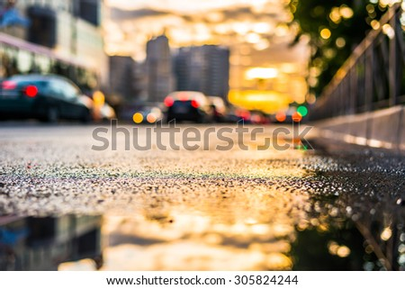 Sun after the rain in the city, view of the cars with a level of puddles on the pavement - stock photo