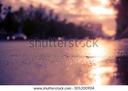 Sun after the rain in the city, view of the cars with a level of puddles on the pavement. Image in the soft orange-purple toning - stock photo