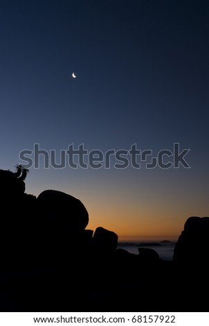 Sun almost completely set behind rock formation, with the moon out in the sky