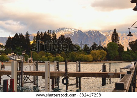 Sun and clouds at sunset within Lake Manapouri, Otago, New Zealand - stock photo