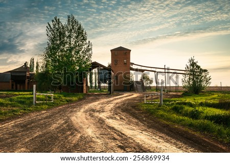 Sun and clouds over field with road. Fantastic landscape - stock photo
