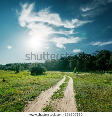sun and clouds over road to wood - stock photo
