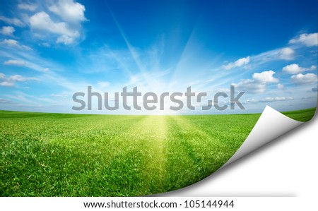 Sun and green fresh grass field blue sky  with folded corner copyspace - stock photo