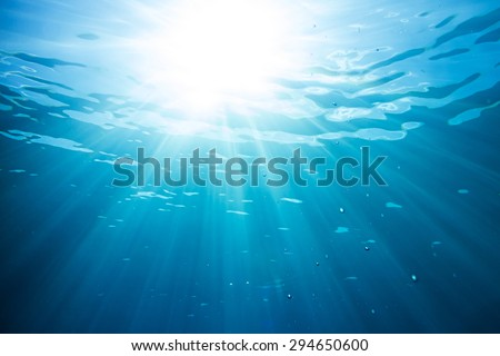 sun and sunbeams underwater shining through the surface - stock photo