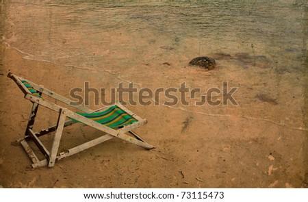 Sun beach chairs on sand near sea in grunge and retro style - stock photo