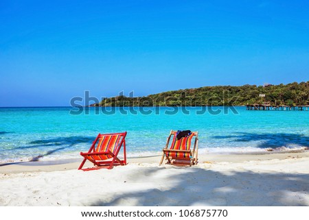 sun beach chairs on shore near sea. Thailand - stock photo