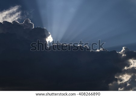 Sun Beams in Dark Clouds and Sky before Thunderstorm - stock photo