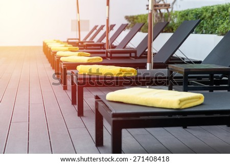 Sun bed beside swimming pool. Vintage filter. - stock photo