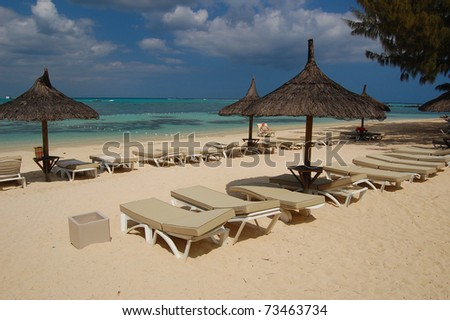 Sun beds and umbrellas on beautiful exotic Mont Choisy beach on Mauritius Island - stock photo