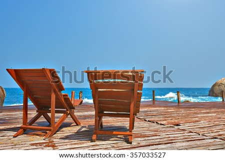 Sun beds on a wooden bridge in the sea tropical islands.