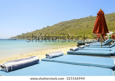 Sun beds with cushions, umbrellas, golden sand and the blue sea in Mykonos, Greece. A greek island summer holiday scene at the Psarou beach with a boat in the crystal clear water over a bushy hill. - stock photo
