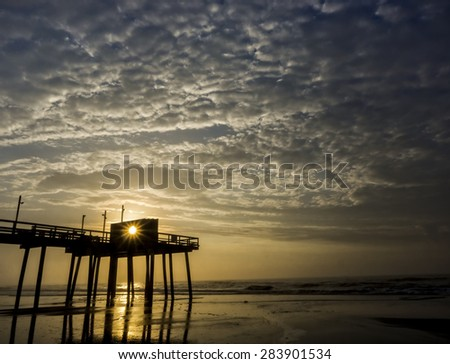 Sun begins to burn through an early morning fog at the Avalon, New Jersey fishing pier on the Atlantic Ocean - stock photo