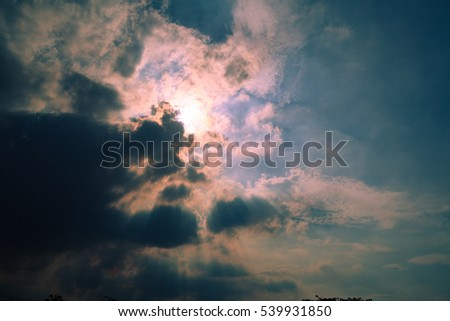 Sun behind clouds with light rays background