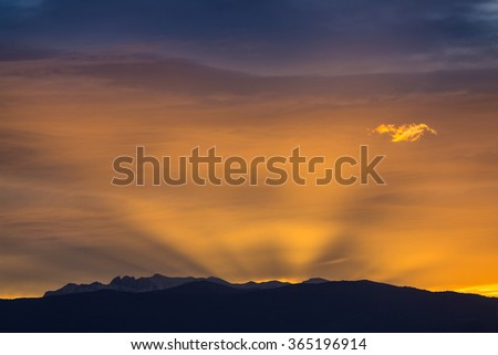 Sun behind dark mountain silhouettes, with colorful sky and clouds - stock photo