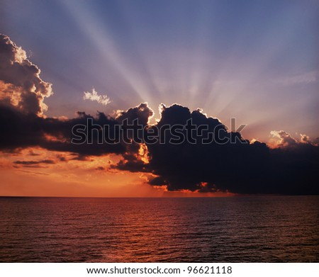 Sun behind dark storm clouds over the Black Sea - stock photo