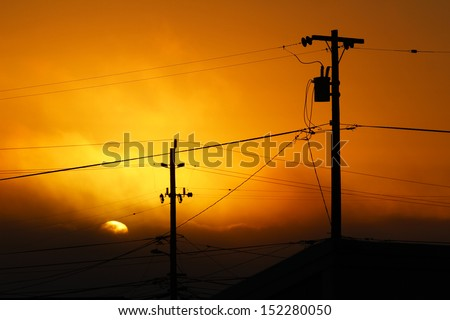 Sun behind telephone poles - stock photo