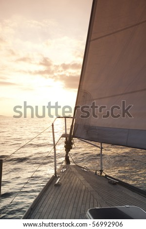 Sun behind white sails - stock photo