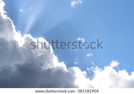 Sun breaking through dark clouds. - stock photo