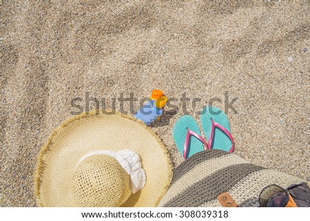sun care  bottle, sandy beach, sandals, straw hat, for background - stock photo
