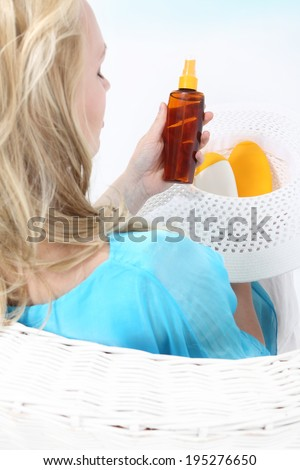 Sun care - cosmetics for tanning . A woman sitting in a basket and reads the beach sun care  - stock photo
