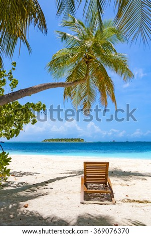 Sun chair in shade of coconut palm tree on tropical beach, view over ocean to an island
