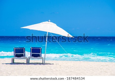 Sun chairs and umbrella on a tropical beach - stock photo