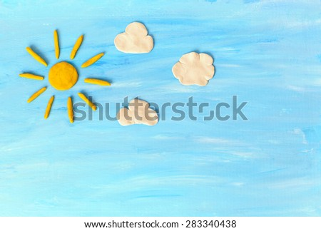 Sun, clouds on blue sky. Made from plasticine - stock photo
