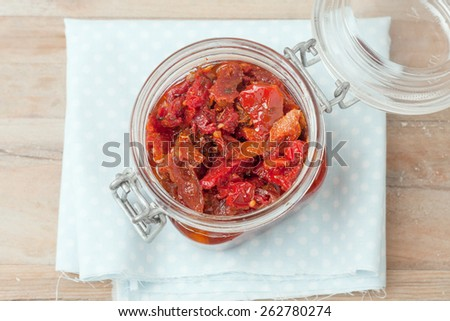sun dried tomatoes in glass jar on wooden background, top view - stock photo