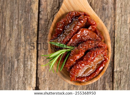 sun dried tomatoes with olive oil on wooden surface - stock photo