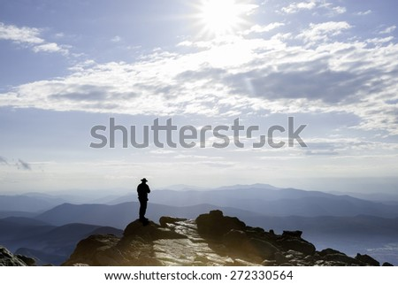 Sun filtered by clouds hits the rocky top on Mount Washington and the silhouettes a man standing looking at view on top, New Hampshire, USA - stock photo
