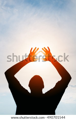 Sun glaring through the silhouetted hands of a man, standing against a cheerful, blue sky.