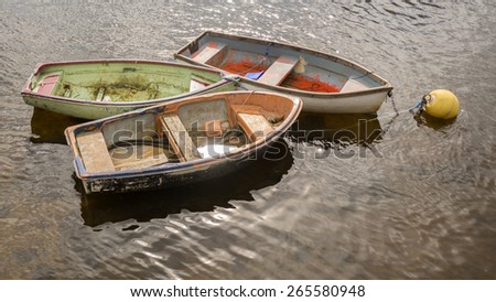 sun glinting off old rowing boats in Scotland, UK - stock photo