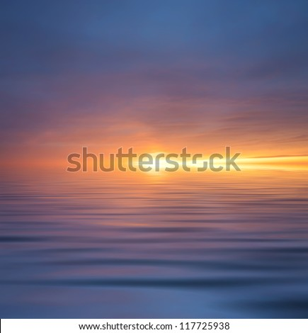 Sun glow and reflection in water surface during sunset. - stock photo