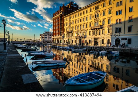 sun goes down and paints colors on the wall of the buildings of Trieste - stock photo