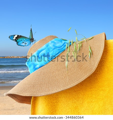 Sun hat and butterfly. Sunny beach colorful accessories with sea landscape in the background - stock photo