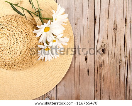 Sun hat and daisies on wooden plank - stock photo