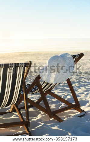 Sun hat hanging from beach chair on sand at sunset; a vacation or retirement concept