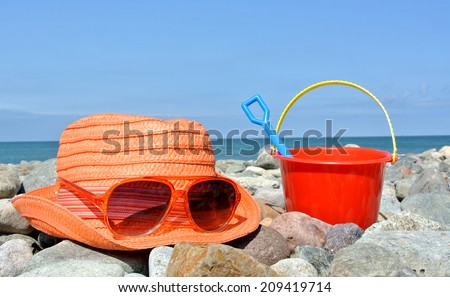 sun hat, sunglasses and bucket with spade on British pebble beach - stock photo