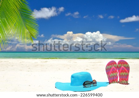 Sun hat with sunglasses and flip flops on white sandy beach -- Concept of tropical vacations - stock photo