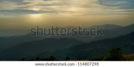 sun hides behind the clouds just before the sunset and last shine rays on alps - stock photo