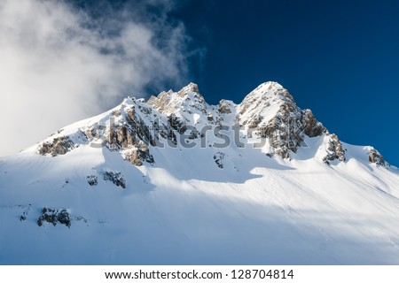 Sun highlighted mountain peak getting covered by a cloud - stock photo