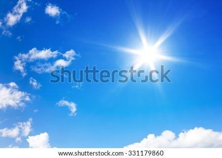 Sun in bright blue sky. - stock photo
