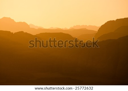 Sun is setting Distant mountains lit by the setting sun in the Wadi Rum desert reservation, Jordan. - stock photo