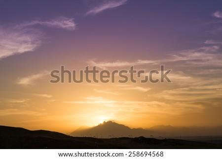 Sun is setting over Sahara desert mountains - stock photo