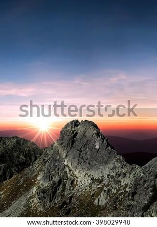 Sun is shining over the mountain peak - stock photo