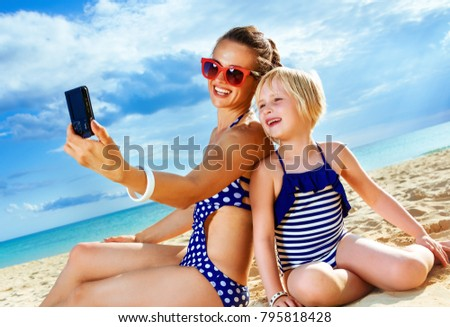 Sun kissed beauty. happy healthy mother and daughter in swimsuit on the seashore with digital camera taking selfie
